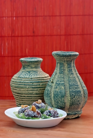 Two handmade vases of terracotta with rum ball in coconut. photo