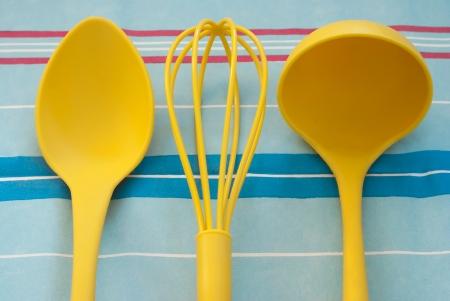 kitchen tools: Gele keuken tools op de blauwe gestreepte tafelkleed Stockfoto