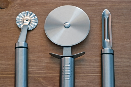Stainless steel kitchen tools on wooden background  photo