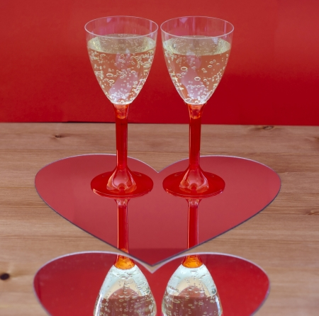 Two champagne glasses mirroring in heart photo