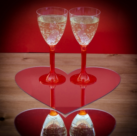 mirroring: Champagne glasses mirroring in heart - vignette view. Stock Photo