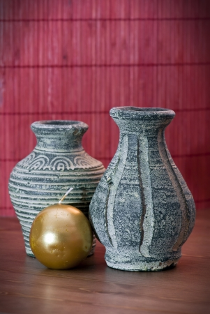 Two handmade vases of terracotta with round candle. photo