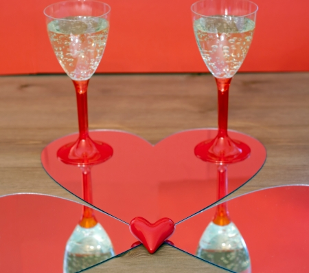 Mirroring of two champagne glasses and little red heart. photo