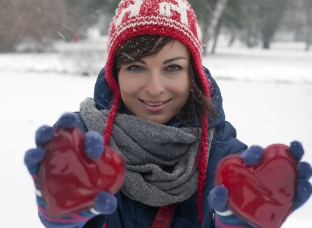 Beautiful woman with two red hearts in the snowy park.  Stock Photo - 17317197