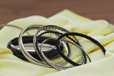 Metal bracelets on a yellow fabric. Stock Photo - 17339889
