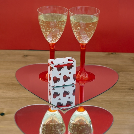 Two champagne glasses and small gift box mirroring in heart. photo