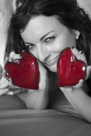 Smiling woman with two red hearts. Colorless photo. Black and white. photo