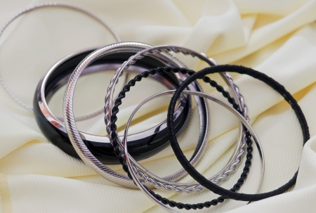Metal bracelets on a background of yellow fabric. Stock Photo - 17386580