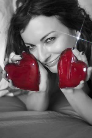 Smiling woman with two red hearts and shimmering earring. photo