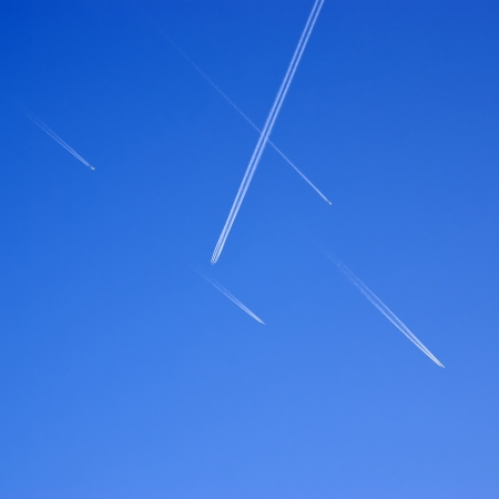 Aircraft traffic. Airliners criss-crossing the blue sky. photo