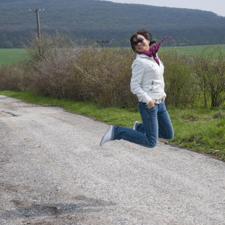 Young woman jumping high with fun. photo