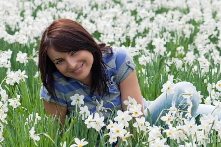 Beautiful woman sitting among daffodils. photo