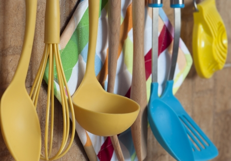 plastic scoop: Set of kitchen tools hanging on the wall.