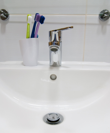 Empty white sink and toothbrushes. photo