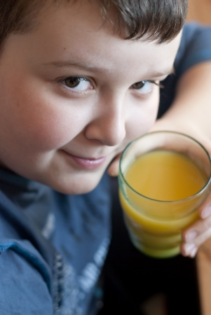 Little boy drinking orange juice and looking up  photo