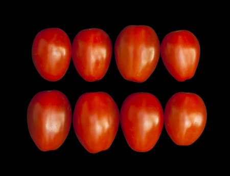 Red cherry tomatoes isolated on a black background. photo
