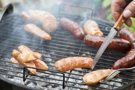 Sausages are baked on a hot grill. photo