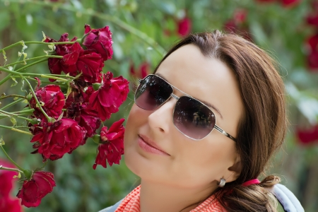 bower: Beautiful young brunette in garden under red roses bower.