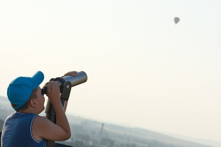 The little boy watching the flying baloon through telescope. photo