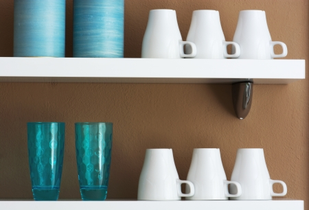 stored: Mugs, cups and jars stored on the shelf. Stock Photo