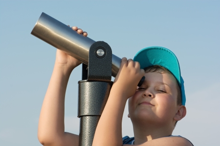 scallywag: Young caucasian boy uses a telescope.