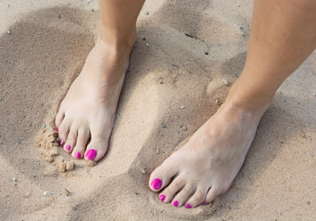 painted toes: Female bare feet in the yellow sand.