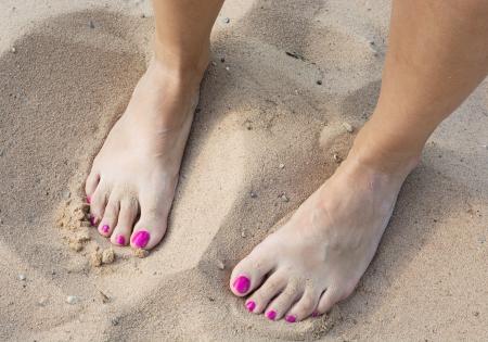 uñas pintadas: Pies desnudos femeninos en la arena amarilla. Foto de archivo