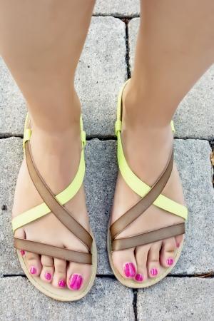 uñas pintadas: Pies de mujer con sandalias de verano.