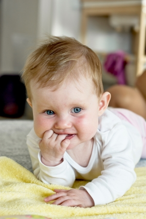 Cute caucasian baby lying on stomach and looking around. photo