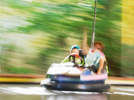 Blurred image of people on the electric car in amusement park.