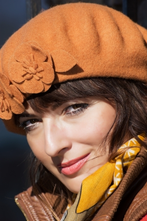 Portrait of beautiful caucasian brunette with the brown cap. photo