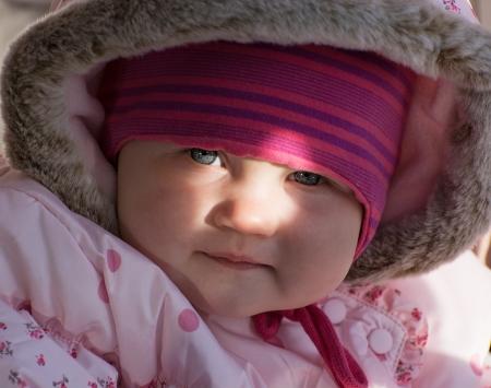 Little baby girl by sun beam illuminates in outdoors. photo