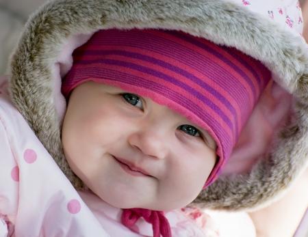 warm clothes: Sorridente caucasica bambina piccola in vestiti caldi. Archivio Fotografico