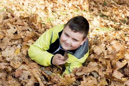 Little caucasian boy plays in autumn dry leaves. photo
