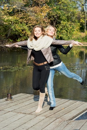 Two attractive young women posing by the pond in the autumn park. photo