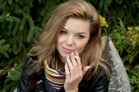 Young caucasian woman smokes a cigarette. photo