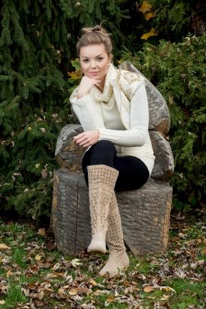 silla de madera: Joven y bella mujer sentada en una silla de madera tallada en el exterior. Foto de archivo