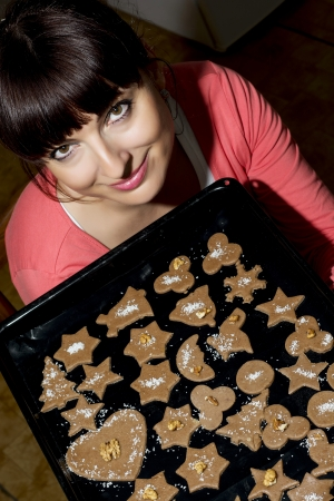 Beautiful young woman holding baking tray with christmas gingerbread cookies. photo
