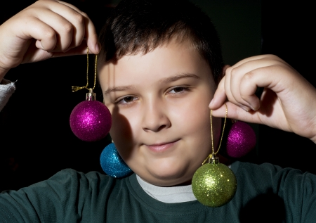 Little caucasian boy showing decorative christmas balls. photo