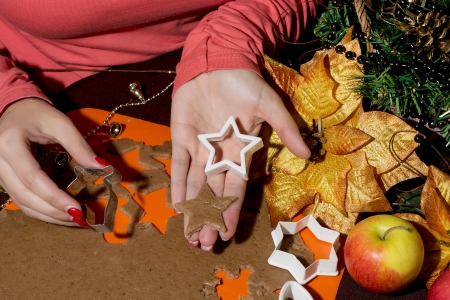 Woman cutting gingerbread christmas cookies from the dough. Star in hand. photo