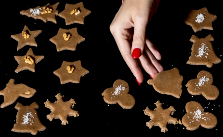 Woman lays gingerbreads on the baking sheet by christmas time. photo