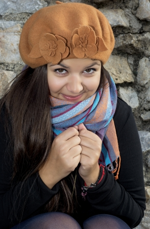 Portrait of young brunette with autumn cap and colorful shawl. photo
