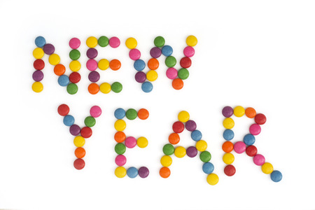 pour feliciter: The title NEW YEAR written of the colored smarties. Festive theme. Stock Photo