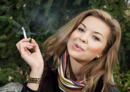 Young caucasian woman smokes a cigarette. Problems of young. photo