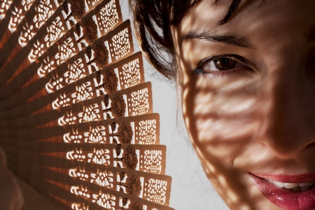 caucasian woman: Beautiful caucasian woman in shadow with a traditional fan. Stock Photo