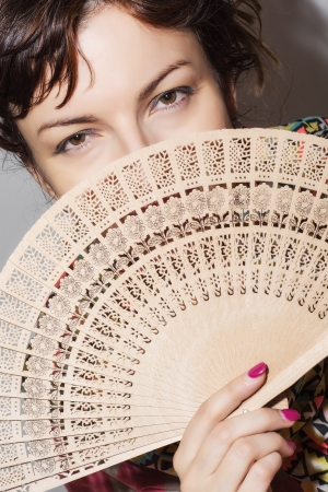 partly: Young caucasian woman partly hidden behind a fan.