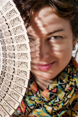 caucasian woman: Smiling caucasian woman peeks out from behind traditional fan.