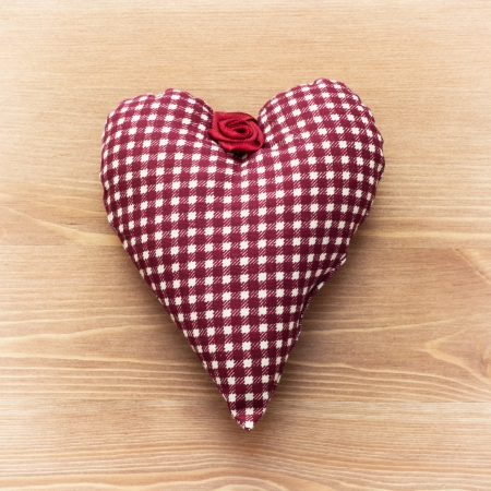 Red heart of fabric on a wooden background. photo