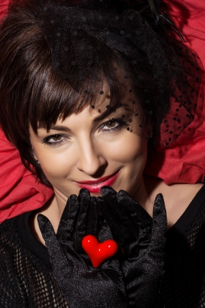Beautiful caucasian woman posing with red heart in hands. photo