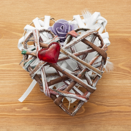 Decorative valentine heart made of paper and fabrics on a wooden background. photo